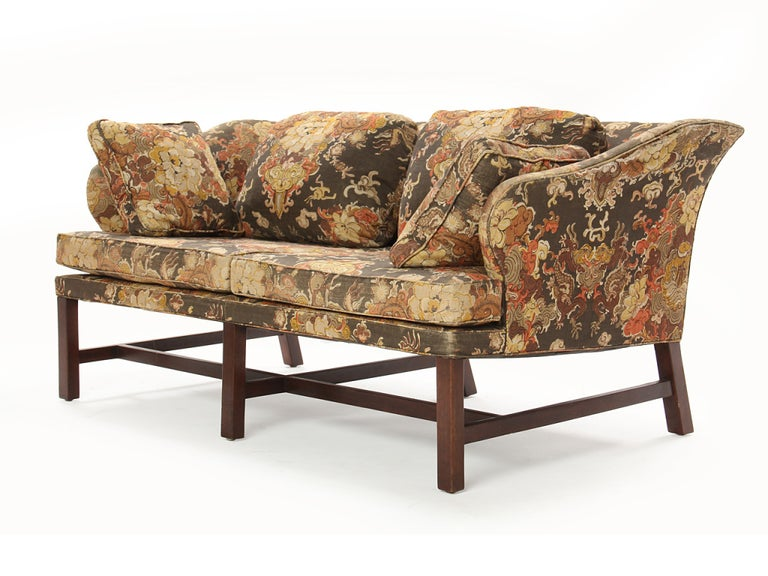 A sofa of English inspiration, retaining the original dark olive, coral, brown and beige stylized Asian influenced floral print linen upholstery, on straight dark walnut legs.