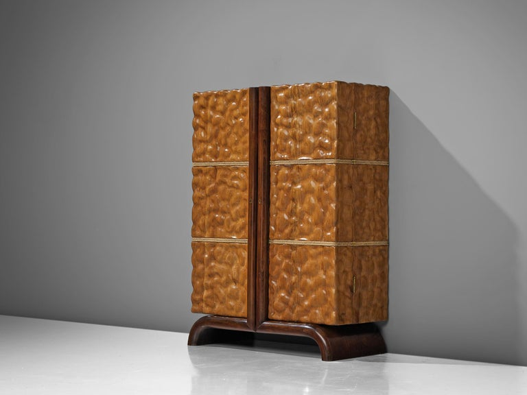 Aldo tura, cocktail cabinet, cherry, mirror, brass, glass and rope, Italy, 1940s  An early bar cabinet, designed by the Italian Aldo Tura. The case piece is made of carved cherry wood, showing a waved surface. The doors are finished with
