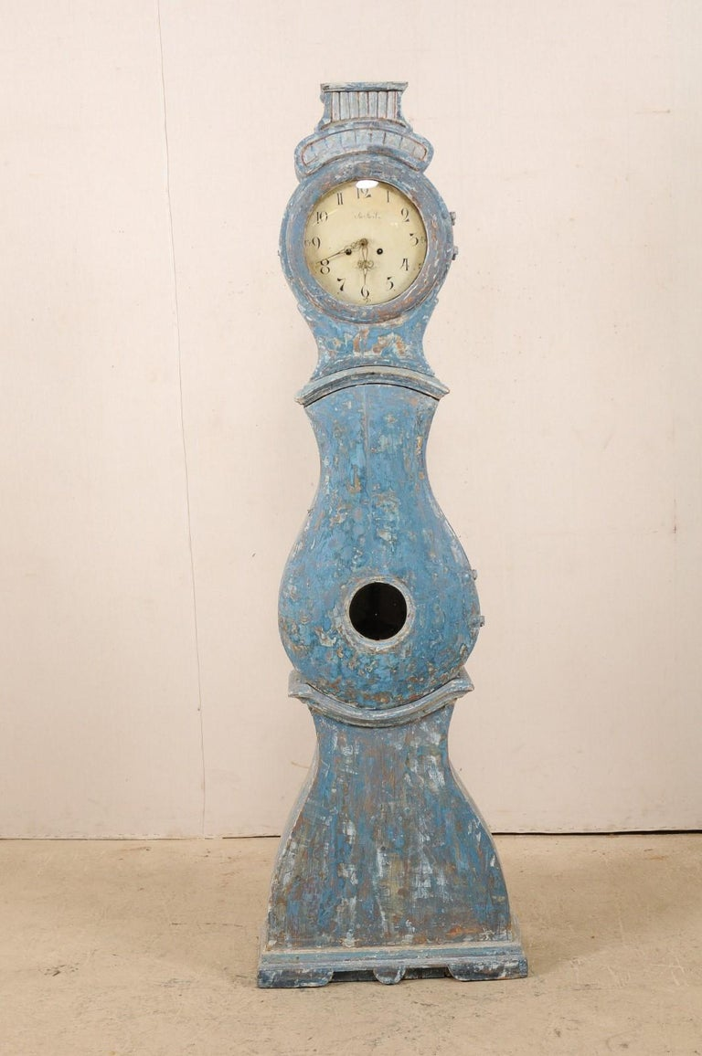 An early 19th century Swedish grandfather clock scraped to its original blue color. This antique tall clock from Western Sweden features a raised bonnet with flattened top, adorned in reeded carvings, atop a round-shaped head, typical tear-drop