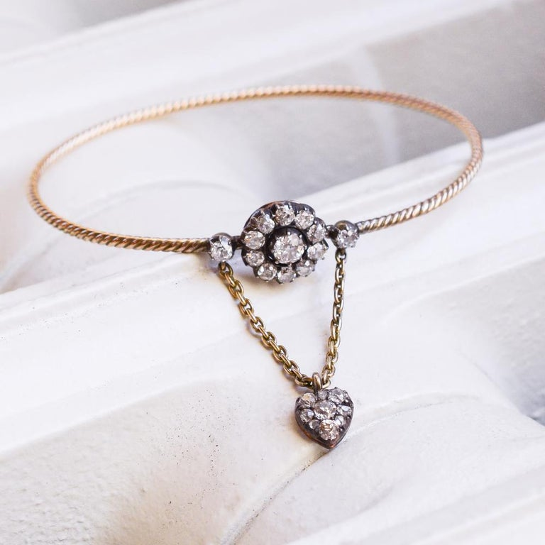 HOLIDAY SALE:  A blossom of old mine diamonds perches on a bangle of twisted rope with the romantic addition of a small diamond heart suspended by a chain from two additional diamonds. The chain functions additionally as a safety chain. The actual