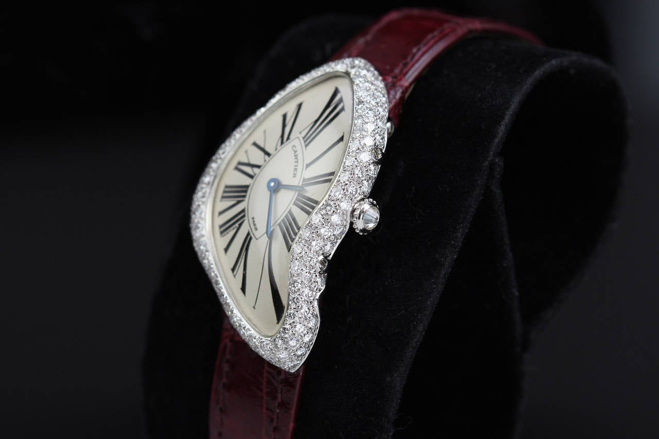 This is an extremely rare version of the Cartier Crash from 2000, signed Cartier, Paris. What makes it so rare are the diamonds. Typically the Crash models from this period did not have diamonds but this particular version does. This is a real