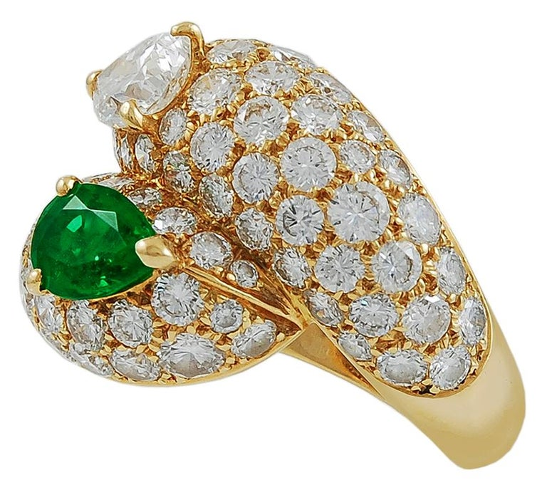 A magnificent 18k yellow gold ring, elegantly set with a pavé of several brilliant cut diamonds that intertwine a radiant pear-shaped emerald and gorgeous pear-shaped diamond. Signed Cartier. Size 53 (6 1/4) Made in France