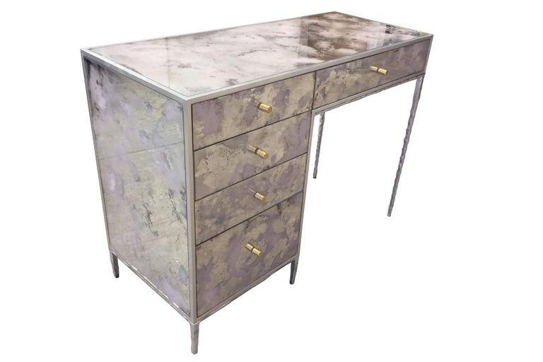 The églomisé pink dust vanity by Ercole Home has a 5-drawer, with silver leaf wood finish. Hand painted églomisé glass panels are inset on the surface.