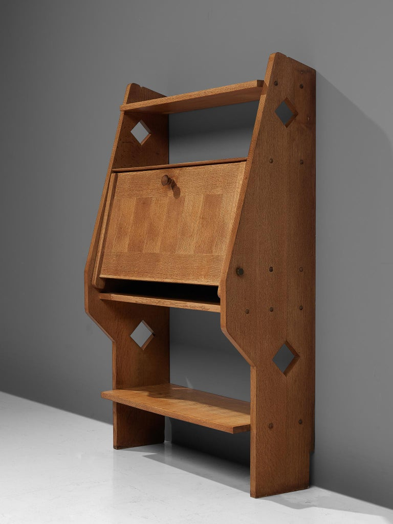 Guillerme et Chambron, secretary, oak, France, 1960s  A solid oak secretary with an inlayed door that flips open and creates a writing space. The sides are have decorative cut outs, typical for the French design duo; Guillerme & Chambron.. This