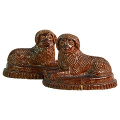 Pair of 19th Century American Yellow Ware Recumbent Spaniels on Oval Plinths