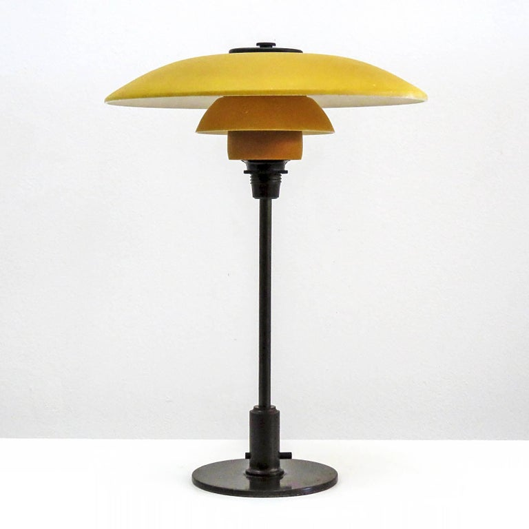Rare Poul Henningsen. PH-3½/2 table lamp with original single-layer yellow painted/opal glass shade set on a browned brass stem and shade holder with wire legs. Bakelite through switch on the stem and bakelite cover plate, produced by Louis Poulsen