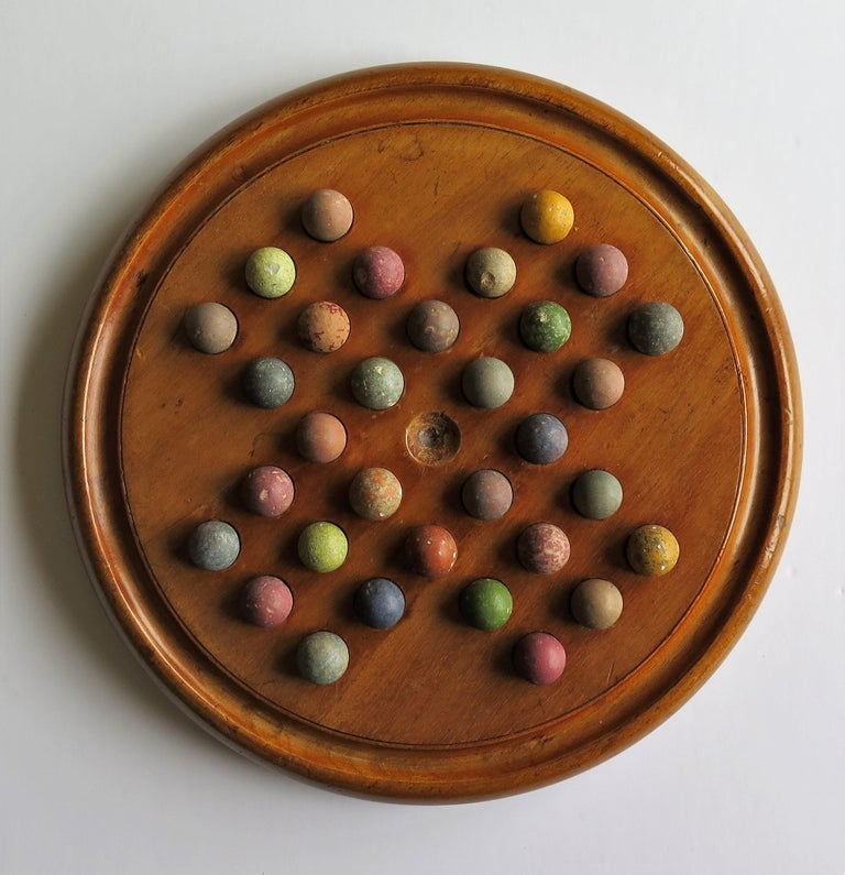 Folk Art Victorian Marble Solitaire Game with Mahogany Board and 32 Handmade Marbles For Sale