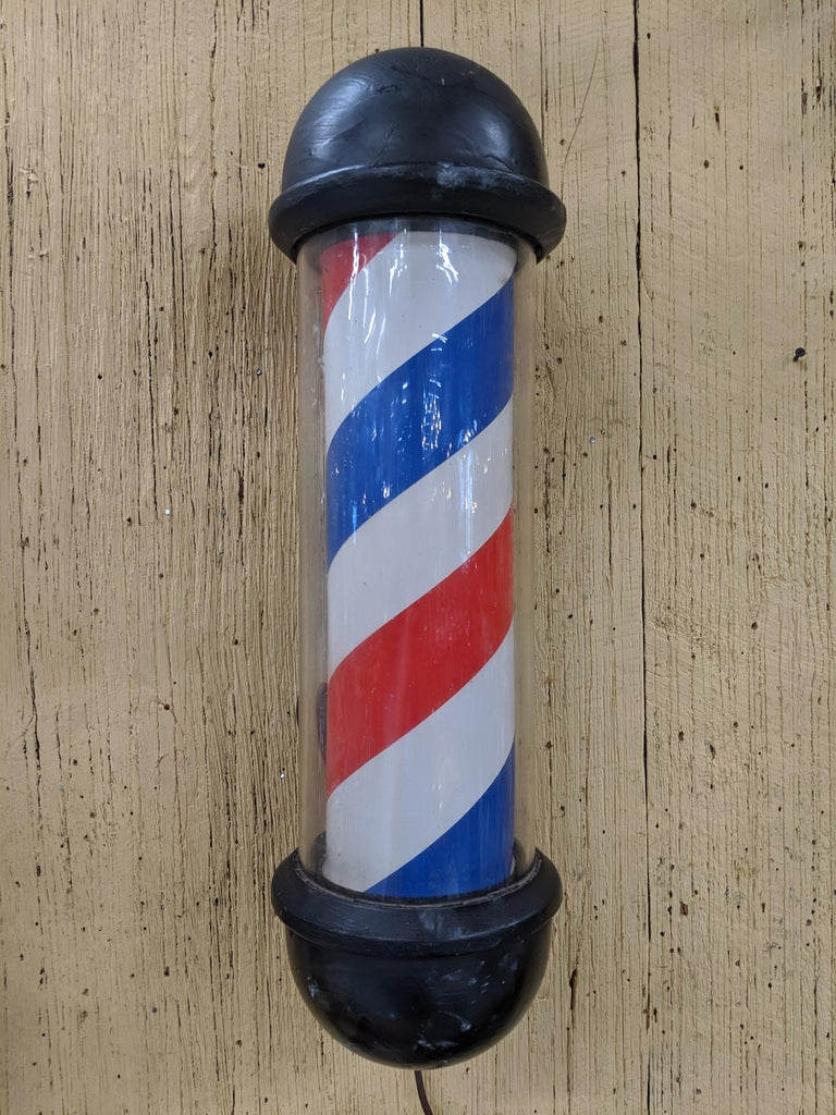 Vintage 20th century wall-mounted barber's pole. All original glass and insert. Black painted cast-aluminum top and bottom. Lights up but inner piece may need adjustment to revolve.