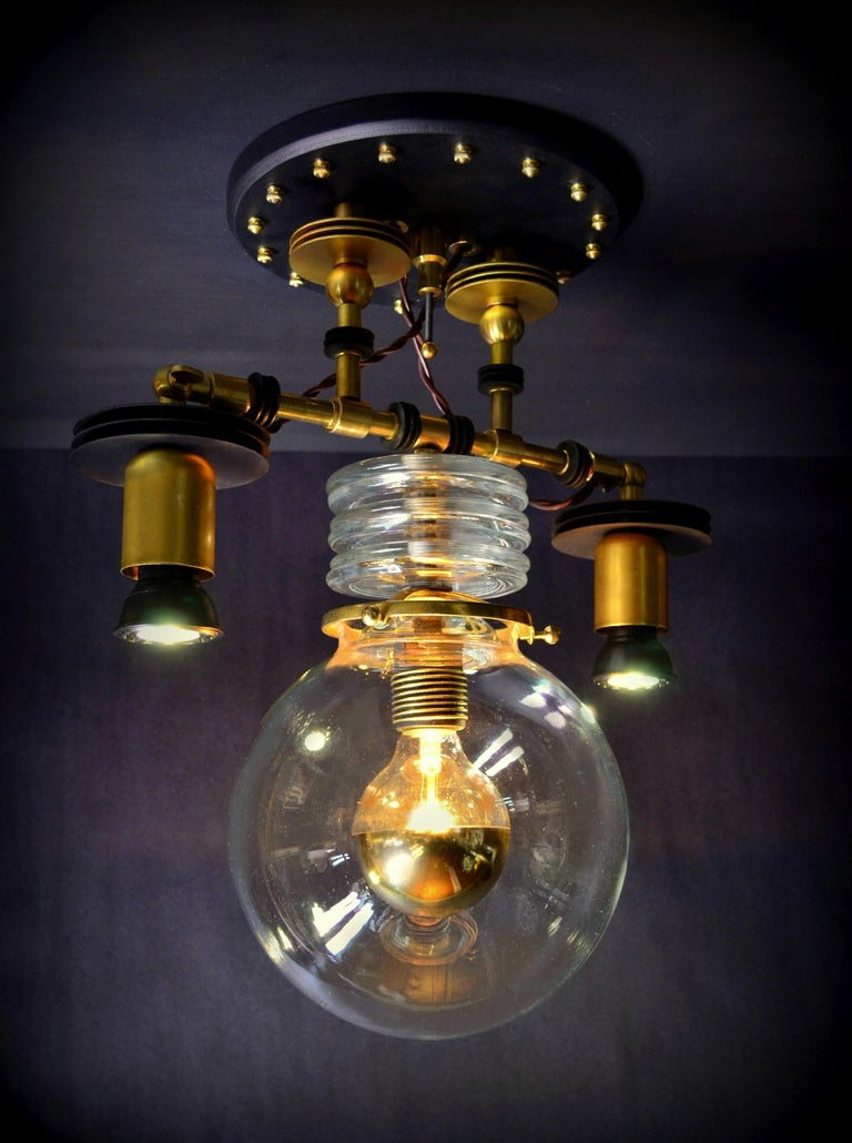 Designed and built by Steampunk master, Art Donovan, the Tesla pendant light features the illuminated center globe with the addition of customized LED spot lights, left and right. High Industrial style. Steampunk with a minimalist pallet in black