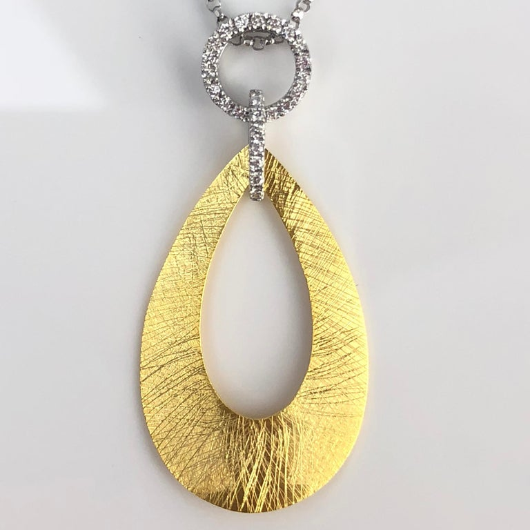 This pendant is a teardrop disc, with a teardrop cutout, with 0.12 carats round diamonds decorating the bail. Set in 14k Yellow and White Gold.  Many of our items have matching companion pieces. Please inquire.  An insurance appraisal certificate