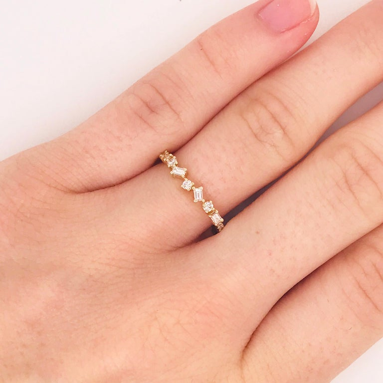 The baguette and round diamond ring is a modern stackable diamond band. With baguette diamonds and round diamonds linked together in a unique form. The fun, quirky design has round diamonds coming from each end in a straight line. There are diamonds