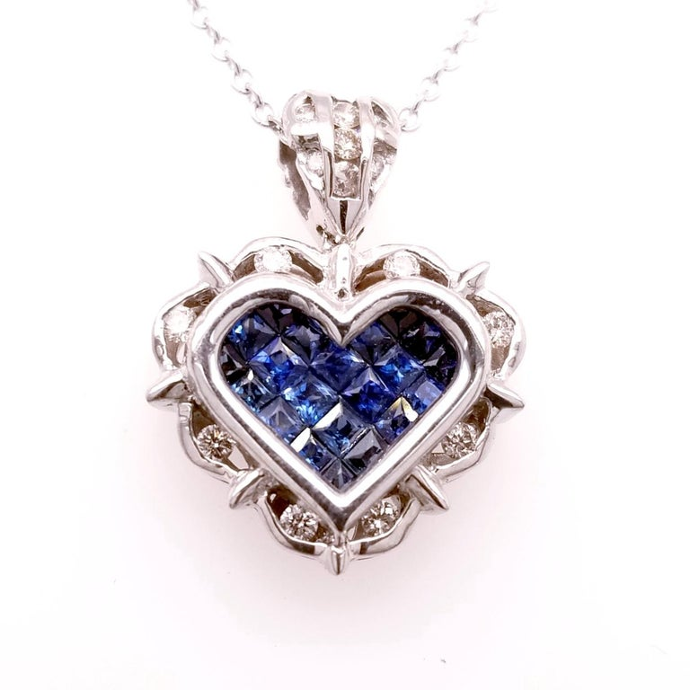 18K Gold Heart shaped Pendant with 21 Invisible Set Princess Cut Blue Sapphires (Total Gem Weight 0.80 Ct) surrounded by a Channel set Halo of diamonds and diamond set Bale with total weight of 0.18 Ct.  Total Diamond Weight: 0.18 Ct Total Gem