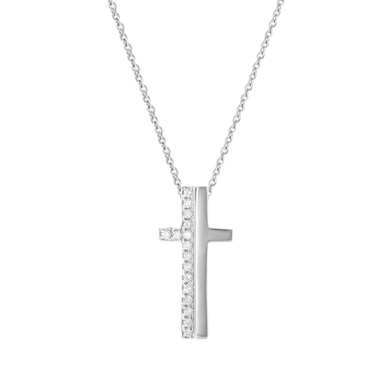 18-karat white gold necklace features a split cross - one side in solid gold, the other accented by 0.21 carats of round brilliant cut diamonds.  Chain length 18 inches.  Pendant height 2.5cm, pendant width 1.3cm.   Composition: 18K White Gold 16