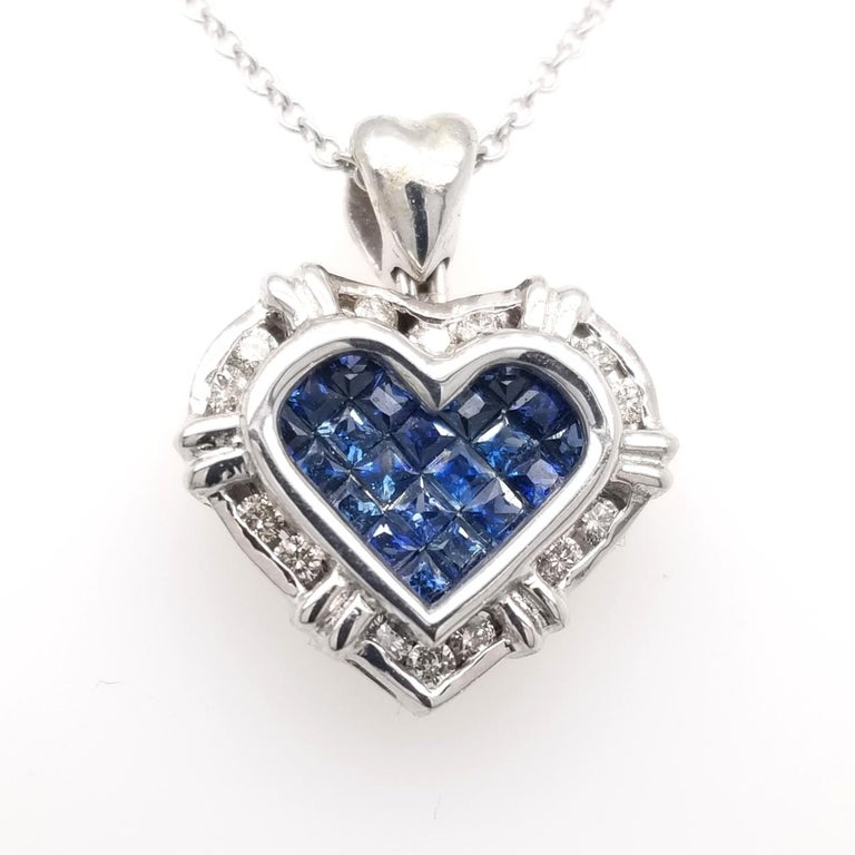 18K Gold Heart shaped Pendant with 21 Invisible Set Princess Cut Blue Sapphires (Total Gem Weight 0.75 Ct) surrounded by a Channel set Halo of diamonds with total weight of 0.24 Ct.  Total Diamond Weight: 0.24 Ct Total Gem Weight: 0.75 Ct Total
