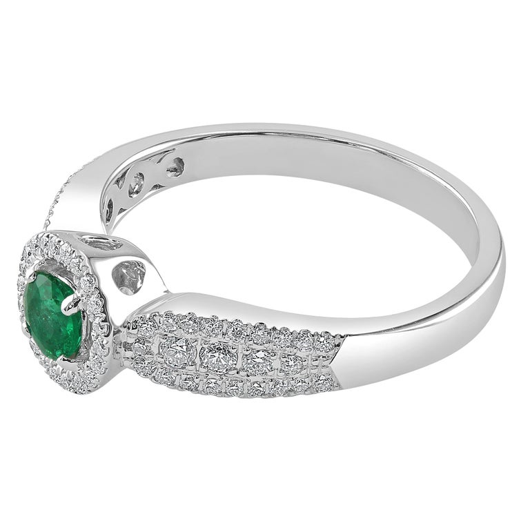 This ring features a 0.24 carat round emerald, surrounded by a halo of diamonds. The Diamonds continue half way down the shank, before tapering off into smooth white gold metal.   This ring would make for an absolutely lovely accessory for any