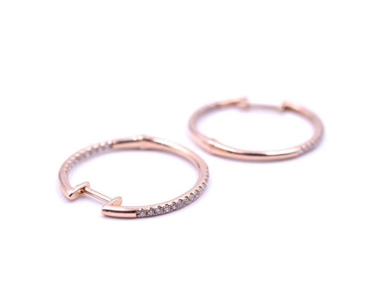 Designer: custom design Material: 14k rose gold Diamonds: 50 round brilliant cut = 0.25 carat weight Color: G Clarity: VS Dimensions: each earring is 21.4mm diameter Fastenings: snap closure Weight: 1.8 grams