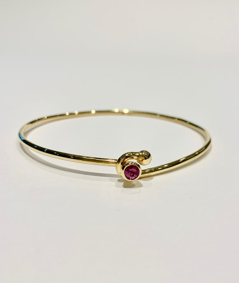 This is a very elegant HANDMADE 18ct Yellow Gold Wire Bangle that has been set with a very feminine 0.25ct Pink Sapphire in a Bezel Set design.   This Bangle would look stunning when worn on its own or also stacked alongside other bangles. We will