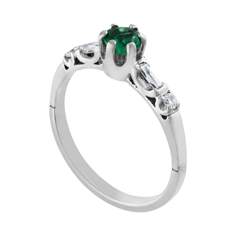 The ring is Platinum The Emerald is a round 0.31 Carat Natural Emerald There are 0.10 Carats in Diamonds F/G VS There are 2 round diamonds and 2 baguette diamonds The ring is a size 6.0, sizable. The ring weighs 3.3 grams
