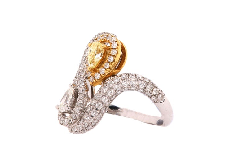 Material: 18k Two Tone Gold Center Stone Details:  1 Pear Shaped Yellow Diamond at 0.36 Carats Mounting Diamond Details: 1 Pear Shaped White Diamond at 0.22 Carats Diamond Details: 130 Brilliant Round White Diamonds as 1.03 carats SI Clarity/H-I