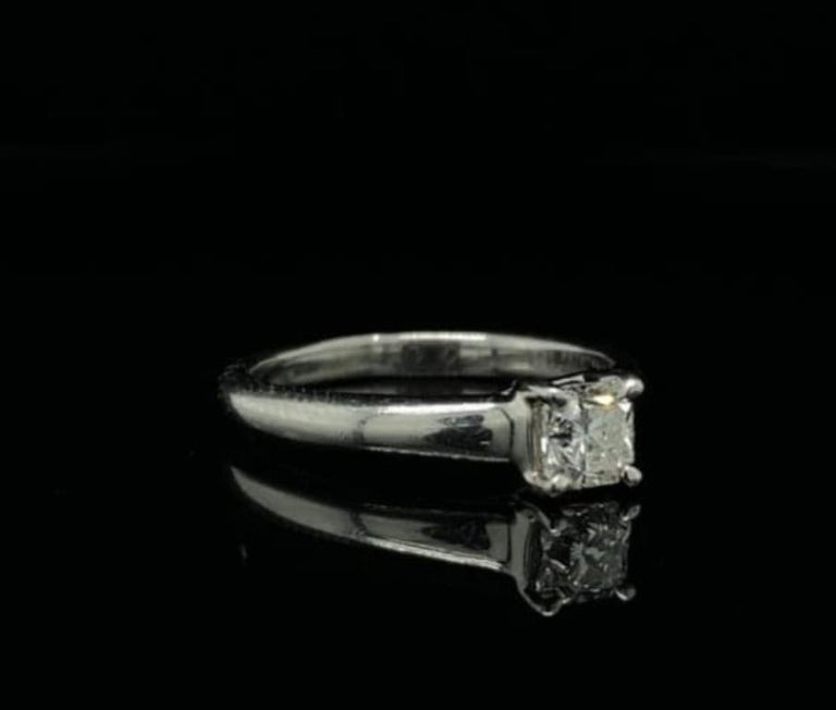A beautiful platinum solitaire engagement ring by Tiffany & Co  From the Tiffany & Co 'Lucida' collection, this ring is set with a 0.49 carat Lucida cut diamond mounted within four claws of sweeping cross-over design on a tapered platinum