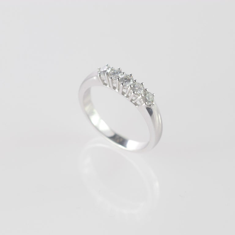 Stunning and marvelous brilliant cut diamond ring embellished by 18 karat carved white gold. Five diamonds for a total of 0.5 carat create a line of gems crafted carefully to be as delicate as the band design. An engagement, bridal or wedding ring