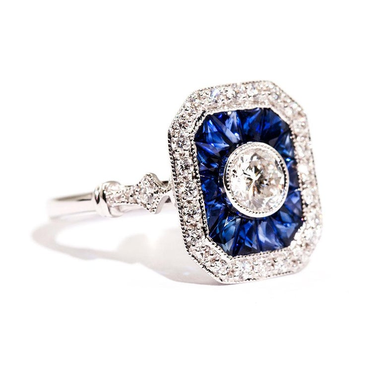Forged in 18 carat white gold is this vintage inspired ring that features a central certified 0.50 carat round brilliant cut diamond that is encompassed with a border of bright deep blue colour custom cut natural sapphires totalling 0.40 carats and