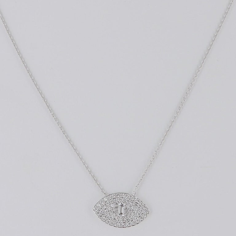 Pendant in the shape of an eye totally paved by diamonds weighing 0,50 carats suspended from a chain (channel) of 40 cm. The Eye necklace is set with one baguette diamond weighing 0.10 Carat and round diamonds weighing 0.40 Carat. The Necklace Chain