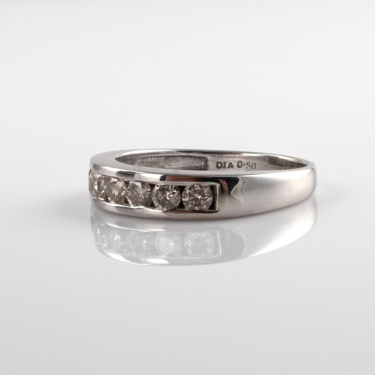 This quality diamond half eternity ring channel set with round brilliant cut diamonds totaling 0.50 carats. Made in 18 karat white gold. Full British hallmarks.  Comes with a neat leatherette gift box for the perfect presentation gift.  Ring size: