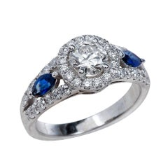 0.50 Carat Round Cut Moissanite Ring with Blue Sapphires in 14 Karat Gold