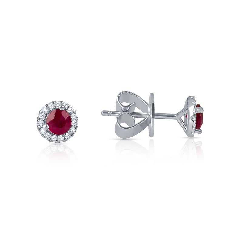 0.51 Carats total weight of round faceted rubies with 0.13 carats of halo accent diamonds. Set into 18K white gold studs with standard friction back post.  Diamond quality: G-H color, SI1-SI2 clarity.