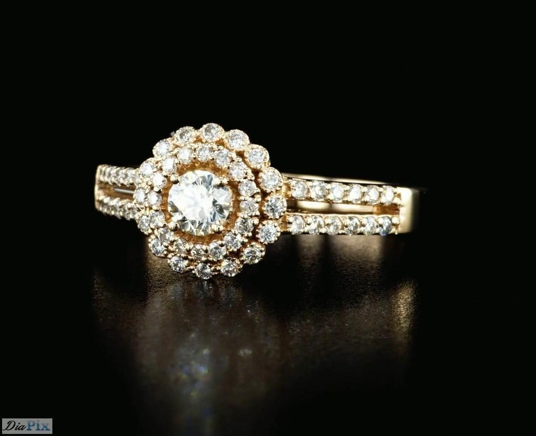 Handcrafted Diamond and Rose gold ring with 0.60 Total Diamond Weight. This timeless ring is set with high quality 0.25 Carat round brilliant diamond E-G/ VS and surrounded by 56 side diamonds 0.35 Carat total weight mounted on 14K rose  gold.