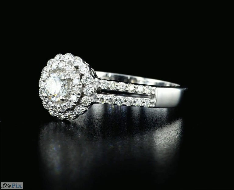 Handcrafted Diamond and white gold ring with 0.60 Total Diamond Weight. This timeless ring is set with high quality 0.24 Carat round brilliant diamond E-G/ VS and surrounded by 56 side diamonds 0.36 Carat total weight mounted on 14K white gold.
