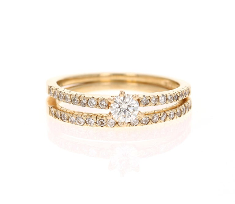 Beautiful Wedding Set in 14 Karat Yellow Gold  The center round cut diamond weighs 0.26 Carats (Clarity: SI1-, Color: H) and is surrounded by 34 round cut diamonds on the shank and on the band that weighs 0.36 Carats (Clarity: VS, Color: H) The