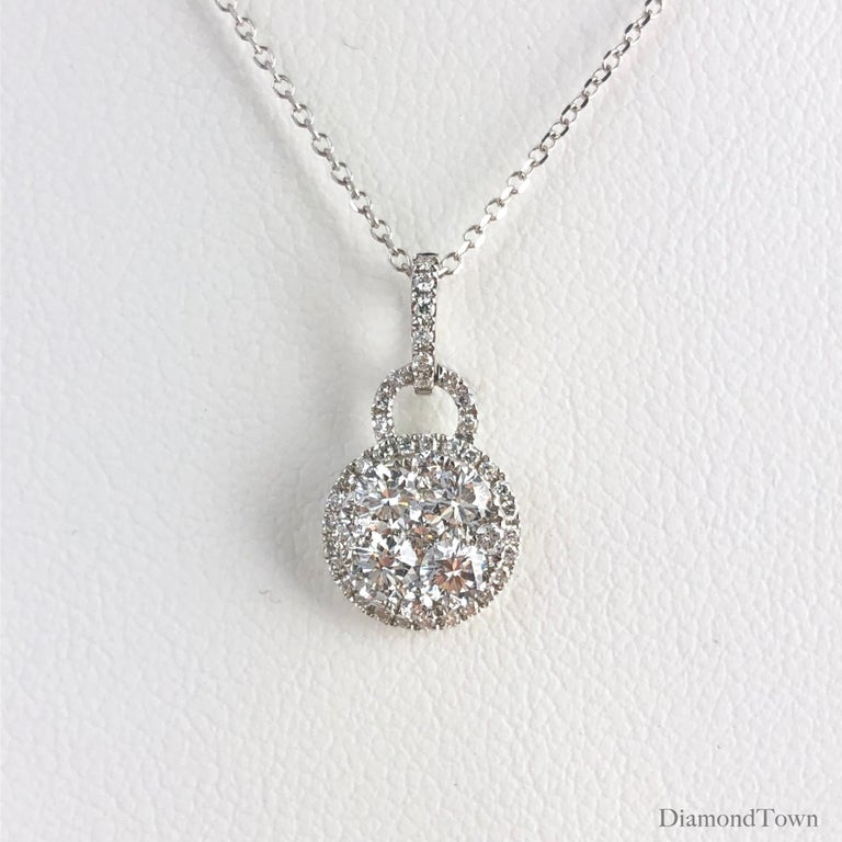 This sweet pendant features a cluster of round diamonds surrounded by a halo of smaller diamonds, as well as diamonds on the bail. Total diamond weight 0.76 carats, set in 18k White Gold.  Many of our items have matching companion pieces. Please
