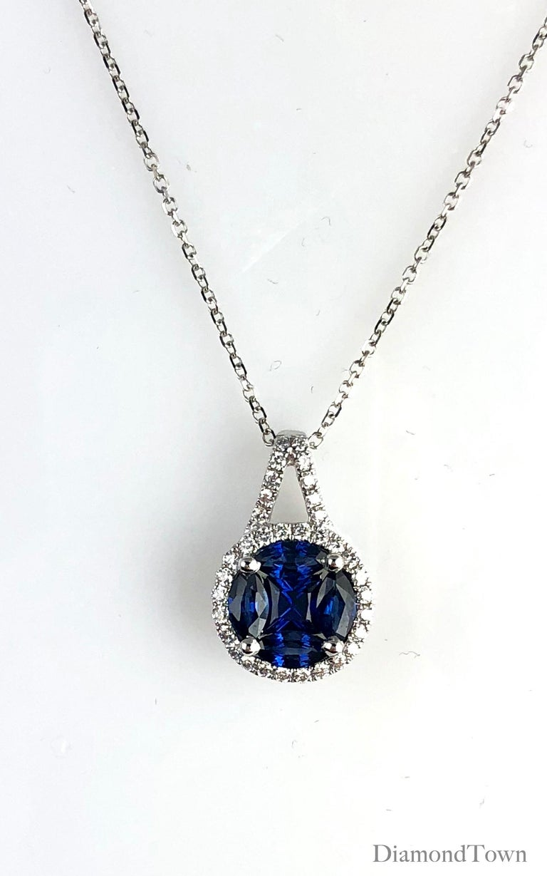 This pendant features a vivid blue sapphire cluster center (5 stones, total weight 0.80 carats) surrounded by a halo of round white diamonds, which also extend up the bail. Total diamond weight 0.19 carats.  Set in 18k White Gold  Matching earrings