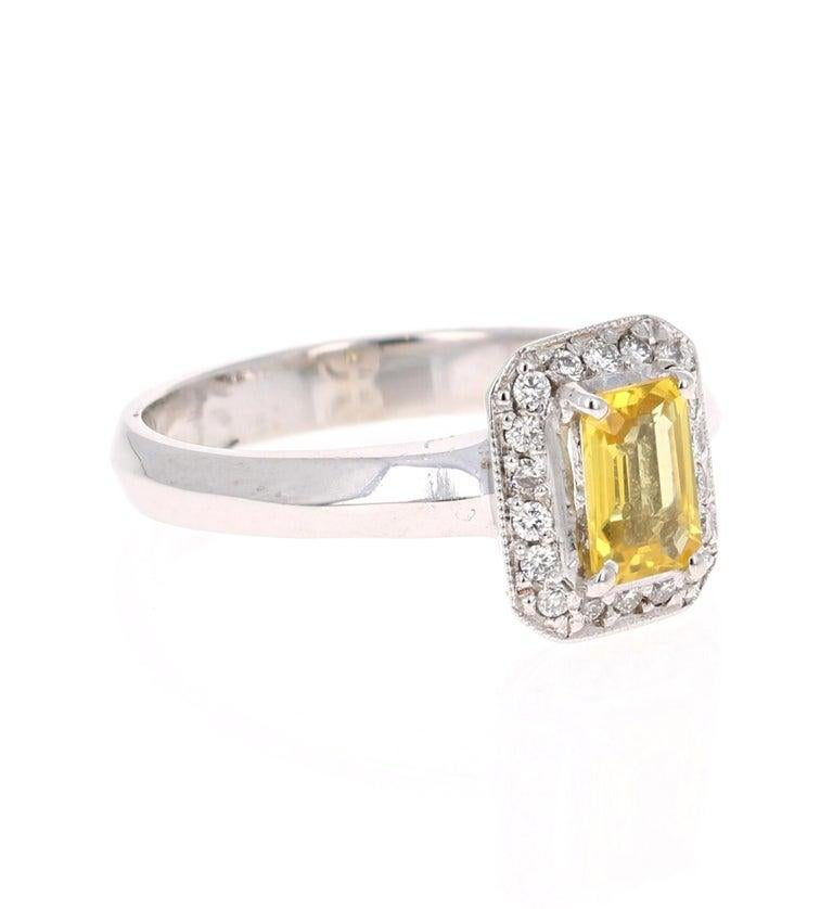This cute ring has a Emerald Cut Yellow Sapphire that weighs 0.66 Carats and is surrounded by 18 Round Cut Diamonds that weigh 0.14 Carats. The total carat weight of the ring is 0.80 Carats.   The ring is set in a cute 14 Karat White Gold setting,