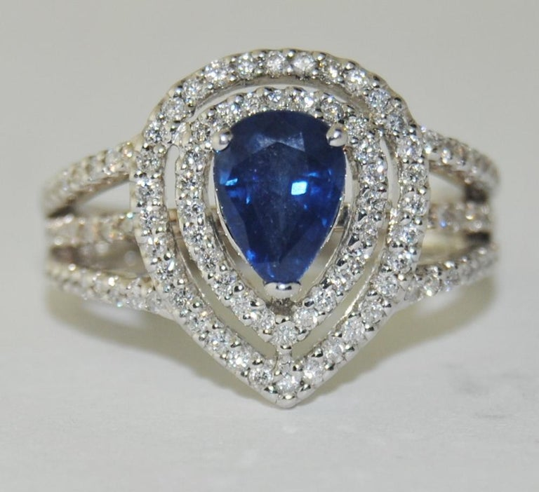 Ladies 0.92 Carat Pear Shape Blue Sapphire Center Ring surrounded by 0.47 Carat Brilliant Round White Diamonds.  This new ring is made of 14 Karat White Gold.  Size 4.75