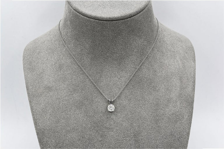 A simple solitaire pendant necklace showcasing a 0.94 carat round brilliant diamond, set in a 14 karat white gold mounting. Suspended on a 16 inch white gold chain made in white gold.  Style available in different price ranges. Prices are based on