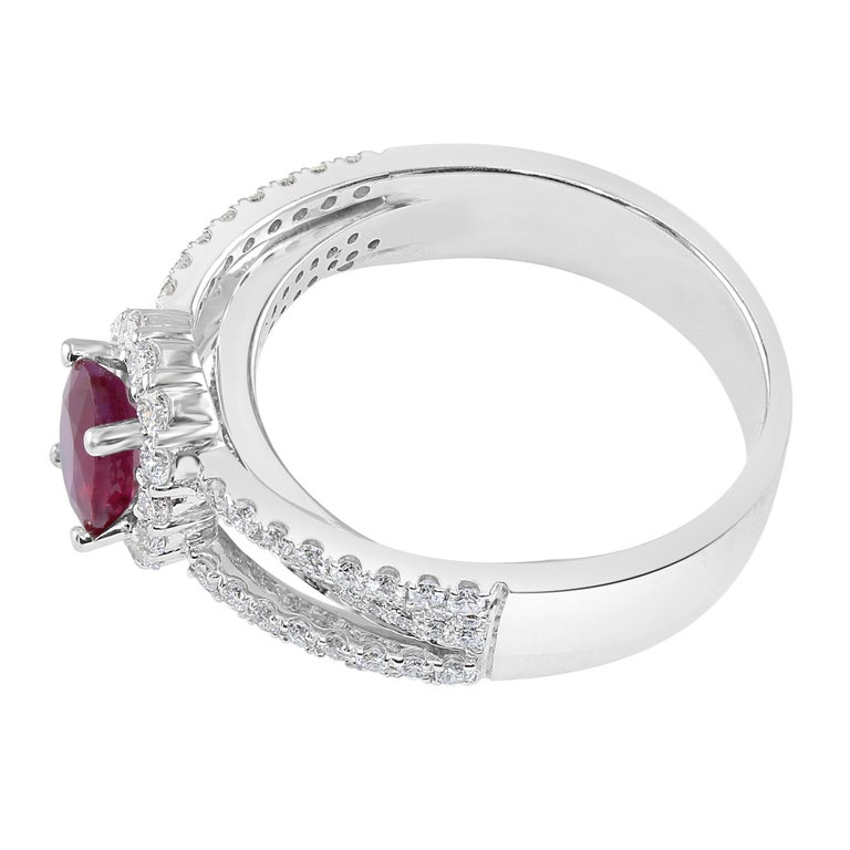 Gorgeous 0.95 carat Oval Ruby, surrounded by a diamond halo.   Total diamond weight: 0.63 carat.  Set in 18K White Gold.  This vivid Ruby is a stunning one-of-a-kind option for a unique engagement ring. May also be worn as a beautiful right-hand
