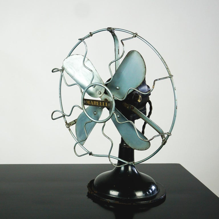 This iconoc Italian table fan has been produced by Marelli ca 1940s. It is in original condition, with some wear and some losses at the base consistent of age and use, preserving a beautiful patina. Please have a look at the photos! It still is