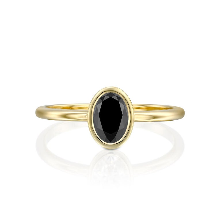 Beautiful minimalistic style black diamond engagement ring ring. Center stone is of 1.5 carats, natural, oval shaped, AAA quality Black diamond. Set in a sleek, 14K yellow gold, solitaire ring with a bezel setting. The setting looks delicate but is