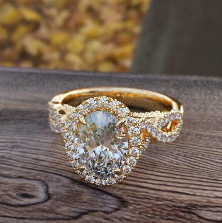 A beautiful diamond engagement ring set made of 14K Yellow Gold set with an oval cut diamond of 1.00ct (can be set with any stone size) accented by white round diamonds. The center diamond of this classic gold ring is a natural SI1 clarity and H