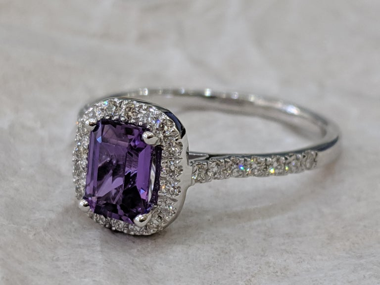 This contemporary Purple Sapphire ring is made of 14k white gold with Emerald -cut central Sapphire of 1.25 carats with Violet natural color, gently holded by prongs above a circle of small white diamonds, making this jewelry unique. This high