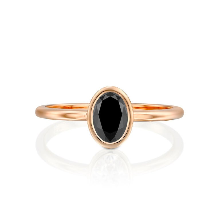 Beautiful minimalistic style black diamond engagement ring ring. Center stone is of 1 carat, natural, oval shaped, AAA quality Black diamond. Set in a sleek, 14K rose gold, solitaire ring with a bezel setting. The setting looks delicate but is