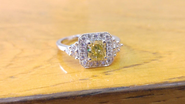 A beautiful square shaped diamond engagement ring made of 14K White Gold set with a fancy yellow diamond of 0.60ct (can be set with any stone size) accented by white round diamonds. The center diamond of this classic art deco halo ring is of