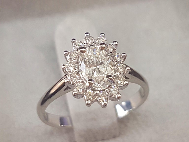 Center diamond is a beautiful 0.70ct F color SI1 Clarity Oval Cut Natural Certified Diamond surrounded by additional micro pave 1/3 carat diamond halo. Cut: Very Good/Excellent Side Stones: 0.50ct F-G VS-SI Diamonds    Main Stone Name: Diamond  Main
