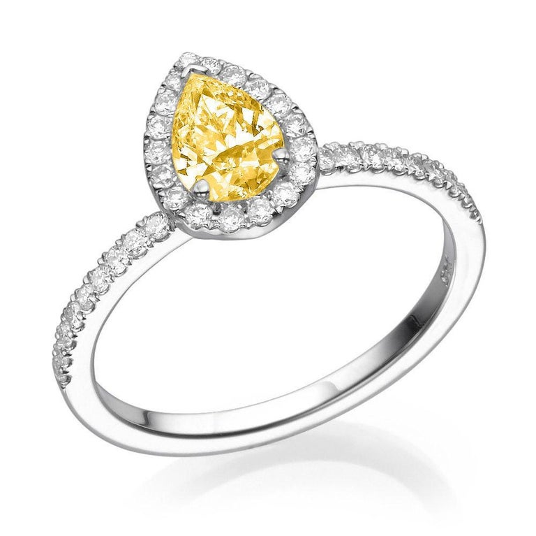 A beautiful vintage pear halo fancy yellow diamond engagement ring made of 14K White Gold set with a Pear cut Diamond of 0.70 carat accented by 36 natural round diamonds. The center stone of this unique engagement ring is of excellent cut , Fancy