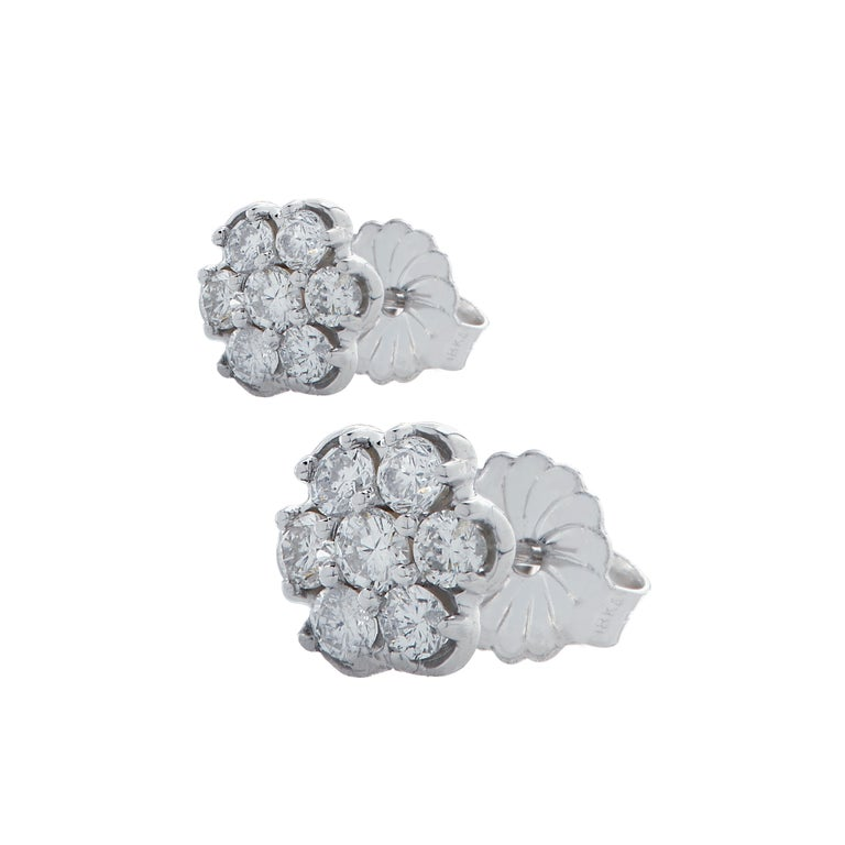 Delightful stud earrings crafted in white gold, featuring 14 round brilliant cut diamonds weighing 1 carat total, G color, VS-SI clarity, arranged in a flower design that captures the unparalleled beauty of nature.  These whimsical earrings measure