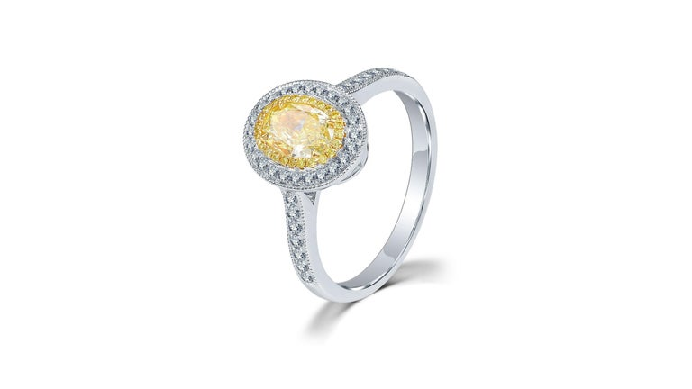 This 1 Carat Fancy Yellow Diamond Ring Oval  cut with 46 white diamonds including  a set down each side of the band.  Its in 18 Karat White Gold If you are looking for anything specific let us know as we can have any custom made.   Do let us know
