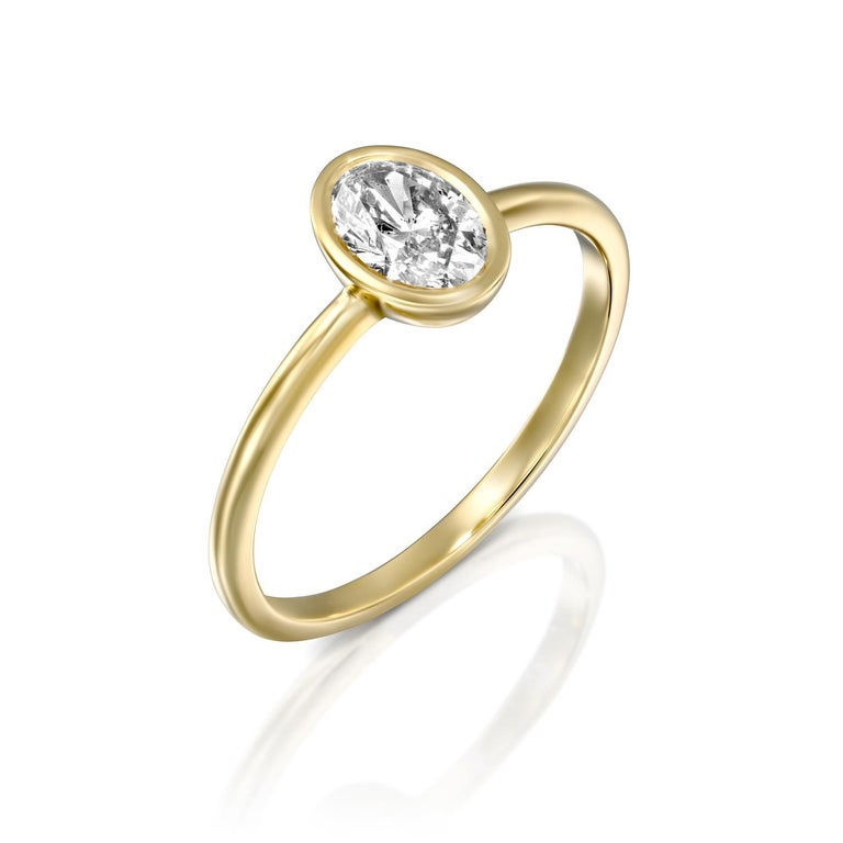 Classic and timeless oval GIA certified diamond engagement ring. Ring features a 1 carat oval cut 100% eye clean natural diamond of F-G color and VS2-SI1 clarity. Set in a sleek, 18K yellow gold, solitaire ring with a bezel setting, this fantastic